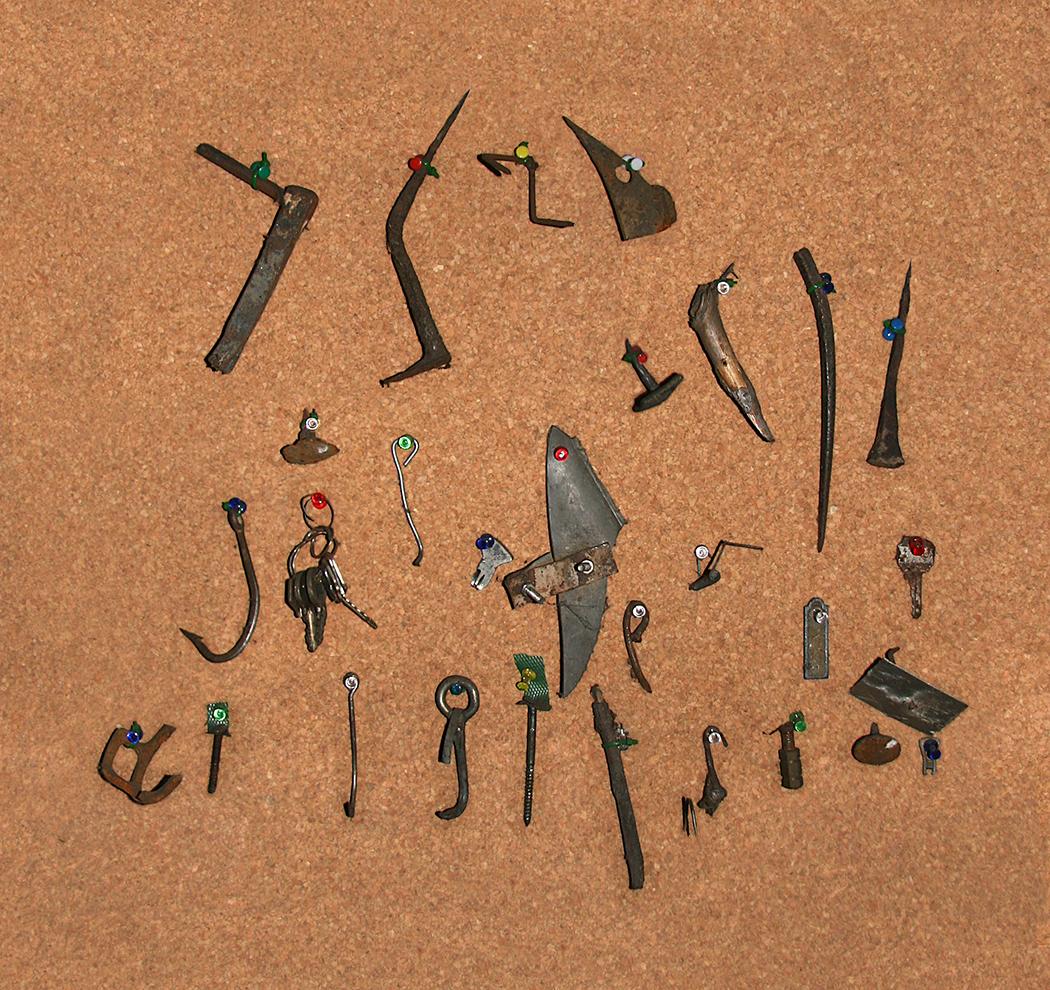 Objetos extraídos de neumáticos pinchados y colgados en la pared del taller por el operario.
