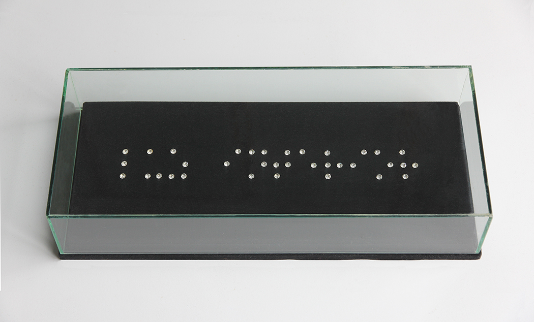 "frase en Braille con cristales de cuarzo : ""Luz interior"".   Terciopelo, vidrio, 42x18x9cm."