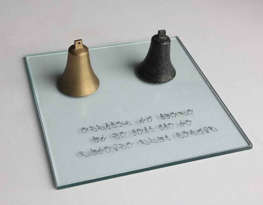 """Campana metálica que suena y otra en piedra maciza. Sobre el cristal, en lenguaje de los sordomudos dice; """"Ecoutez la Pierre. Il ce peut que le silence sois dedans"""". 36x36cm"""
